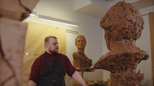 A Man Sculpting a Clay Statue