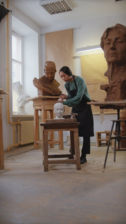 Woman Working on a Sculpture Using a Chisel and Hammer