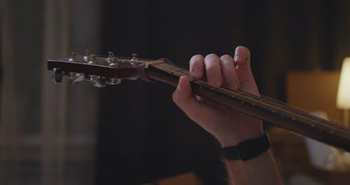 Man Playing Guitar while Lying Down