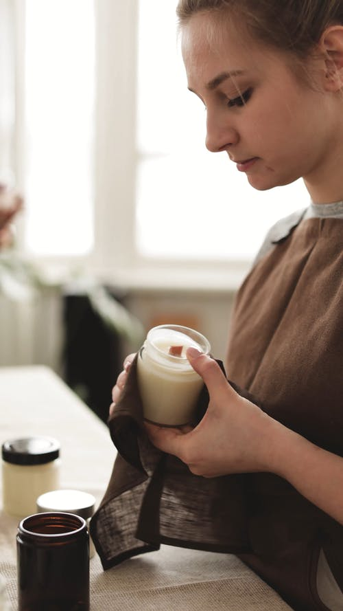 Woman Wiping Off Candle Jar