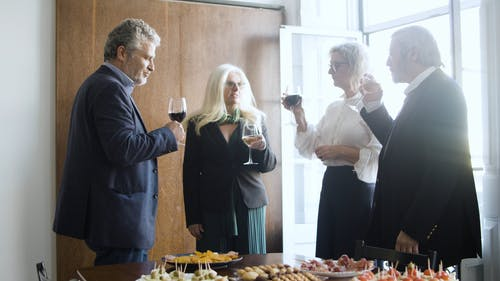 People Talking While Holding Wine Glass