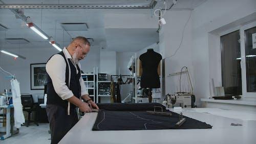 A Man Cutting Cloth Using a Pair of Scissors