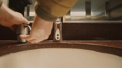 Person Washing Hands in the Sink