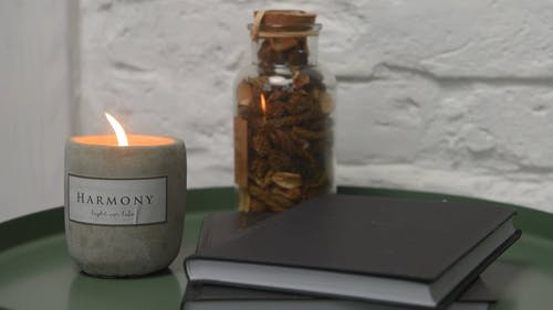 Close-Up View of Candle, Notebook, and Bottle