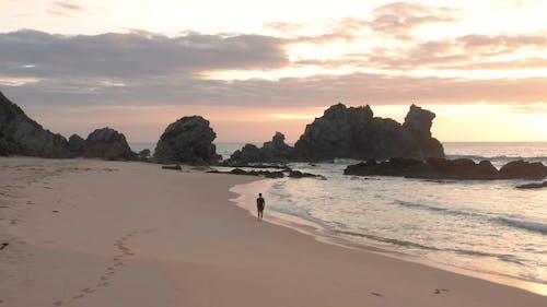 A Man Walking on a Beach During Sunset