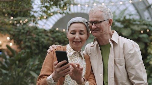 Couple Having Fun Browsing Their Smartphone