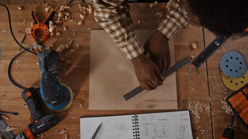 A Person Marking a Piece of Wood