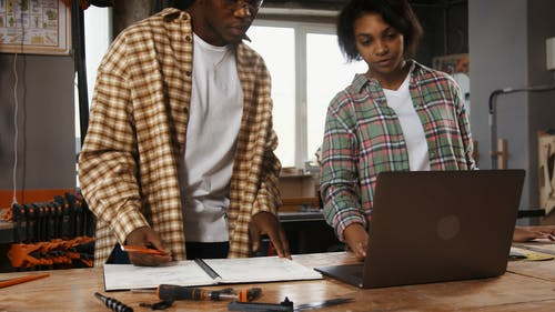 Young Man and Woman Using Laptop and Taking Notes