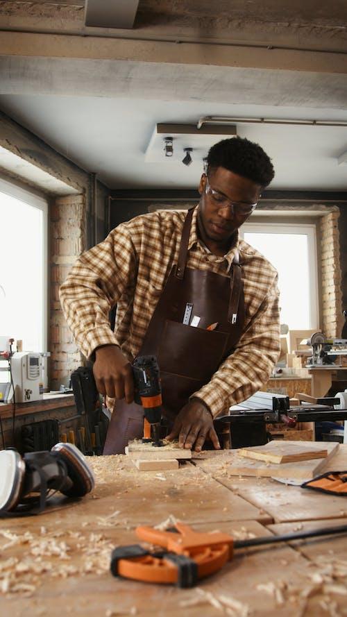A Man Drilling a Wood