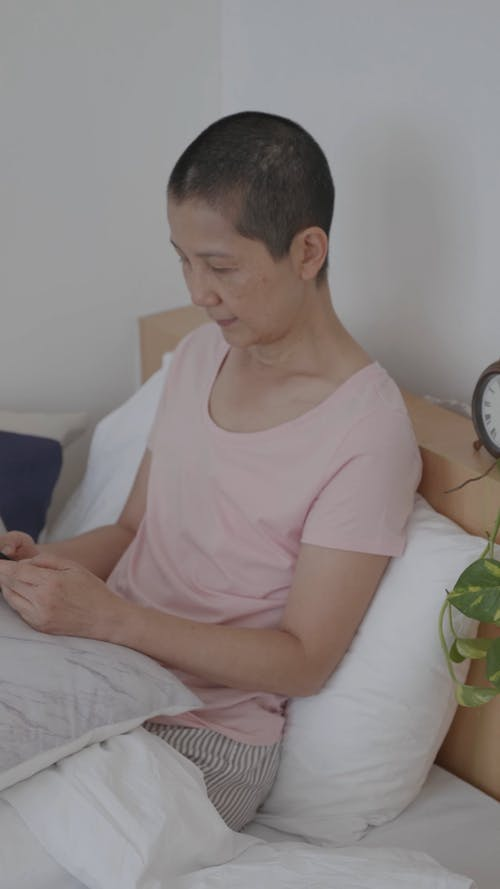 Woman Sitting on Bed Using a Phone