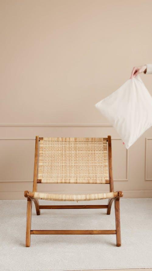 Person Placing Cushion On An Arm Chair