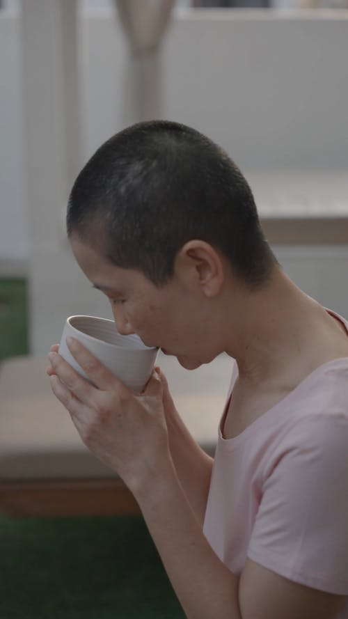 Woman Drinking in a White Cup