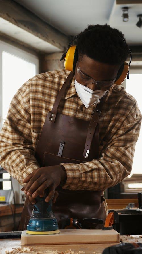Man Polishing Piece of Wood