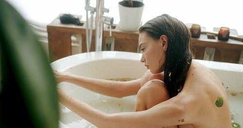 A Naked Woman Sitting on a Bathtub