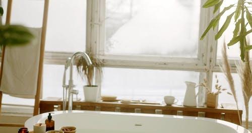 Woman Putting Bath Salt in a Bathtub
