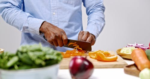 Men Chopping Vegetables In The Wooden Board
