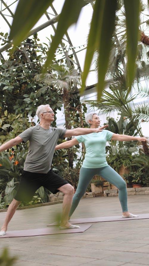 Couple Doing Yoga in a Botanical Garden