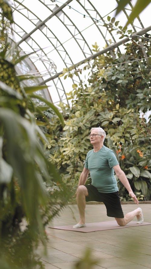 Man Doing Yoga in a Botanical Garden