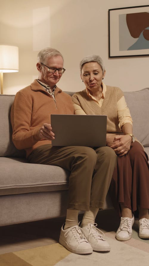 Couple Talking to Each Other While Looking at a Laptop