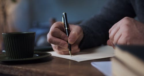 Elderly Man Writing on a Piece of Paper