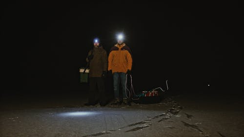 Men with Flashlights Standing Outdoors at Night