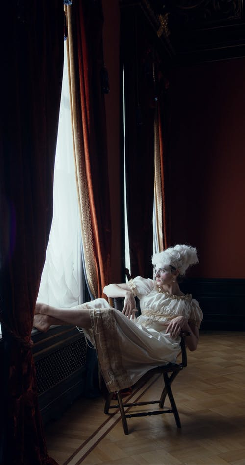 A Person in Costume is Sitting Beside the Window