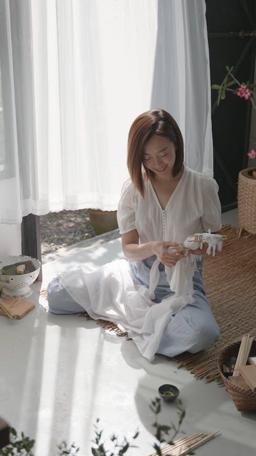 Young Woman Tying Chopsticks to Fabric