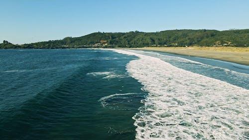 An Aerial Footage of Ocean Waves on a Beach