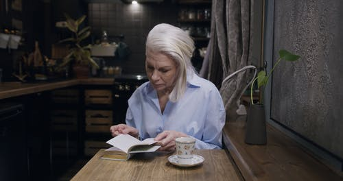 An Elderly Woman Reading a Book While Drinking Tea