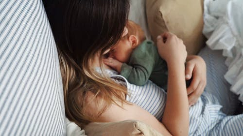 A Mother and Her Baby Lying in the Bed