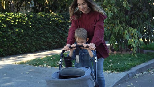 Mother and Son Pushing the Baby Stroller