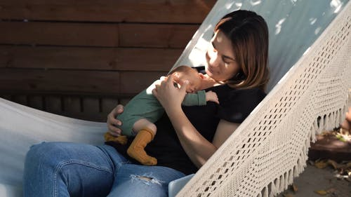 Mother Holding a Baby while Sitting on a Hammock
