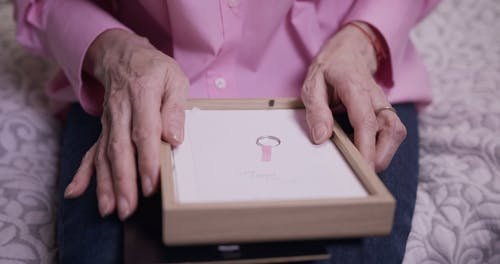 Elderly Woman in Pink Long Sleeves Wears Her Ring