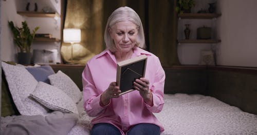 Elderly Woman in Pink Long Sleeves Holding a Photo Frame