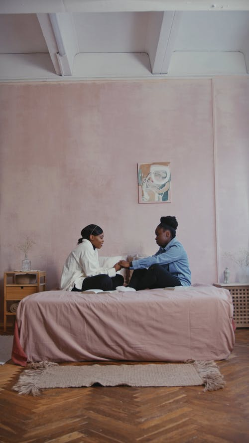 Women Sitting on the Bed while Praying Together