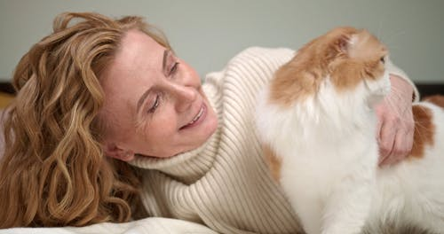 A Woman Petting Her Cat On Bed
