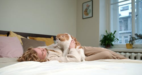 A Woman Petting Her Cat On The Bed