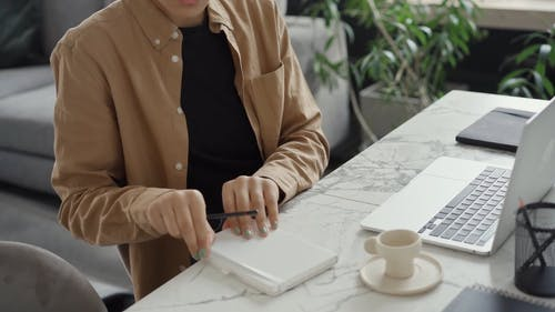 A Woman Writing in Her Notebook and Checking Her Laptop