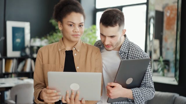 Man And A Woman Looking At A Tablet S Screen