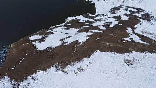 A Footage of a Snow Covered Cliff