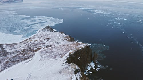 An Aerial Footage of a Snow Covered Cliff
