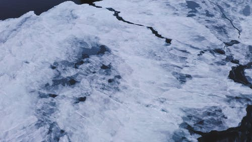 A Footage of an Ocean with Snow and a Snow Covered Cliff