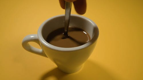 Person Stirring a Cup of Coffee