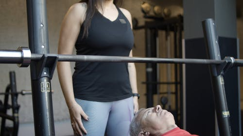 A Woman Assisting A Man Doing Bench Press with a Barbell Rod