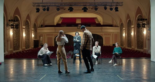 Actors Rehearsing On Stage With The Production Team