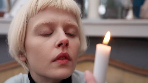 A Woman Staring at a Flame of a Candle