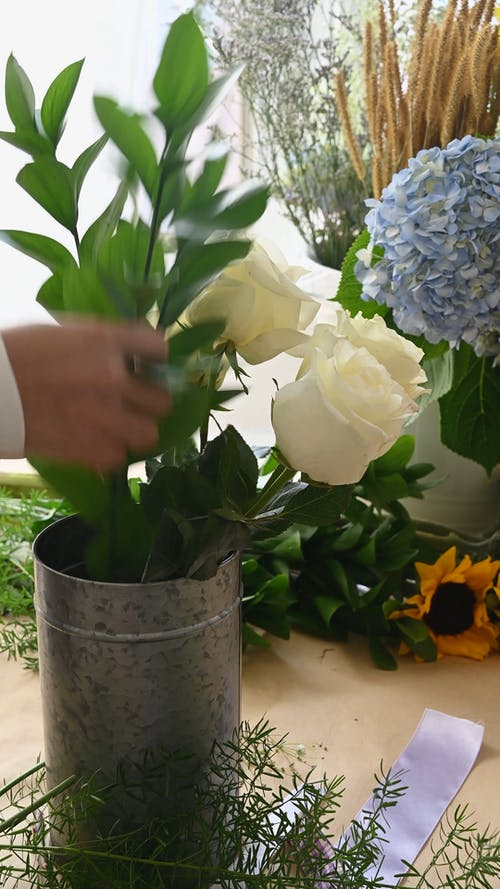 Person Arranging Flowers in a Tin Can
