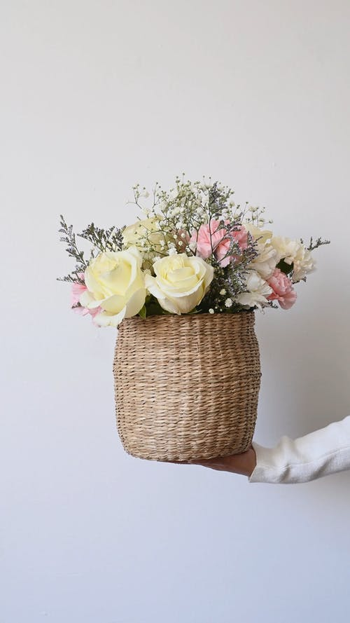 Person Holding a Basket Full of Flowers
