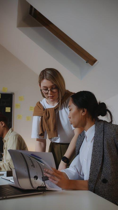 Women Brainstorming while Using Laptop