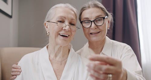 An Elderly Couple Wearing Eyeglasses while Talking to Each Other